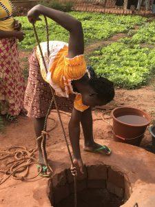 Jeune fille puisant de l'eau